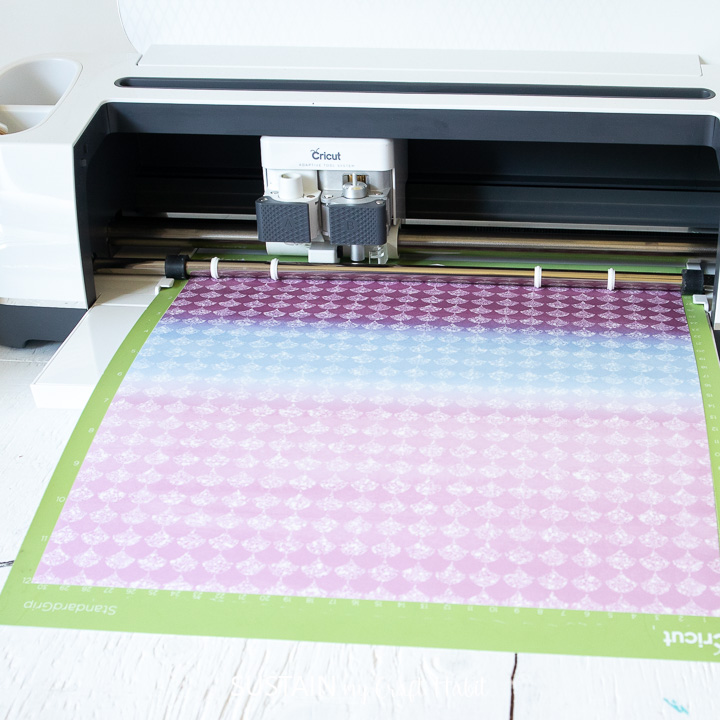 Loading an infusible ink transfer sheet into the Cricut machine.