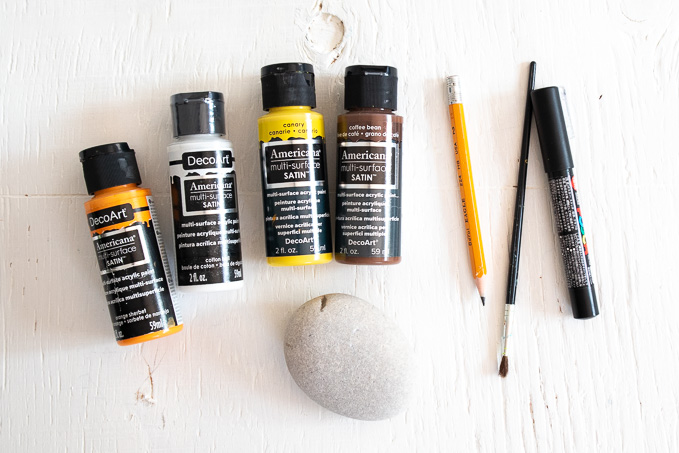 Supplies needed to paint sunflower rocks including stone, paints, pencil, brush and paint pen.