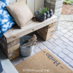 photo of a front porch with a painted welcome mat and seating area