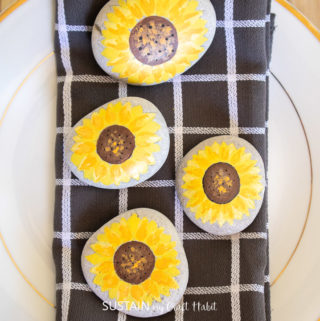set of 4 painted sunflower rocks styled on a napkin