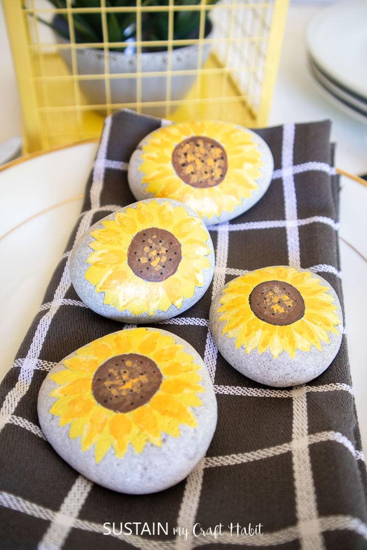 Pretty sunflower painted rocks on top of a dinner plate setting.