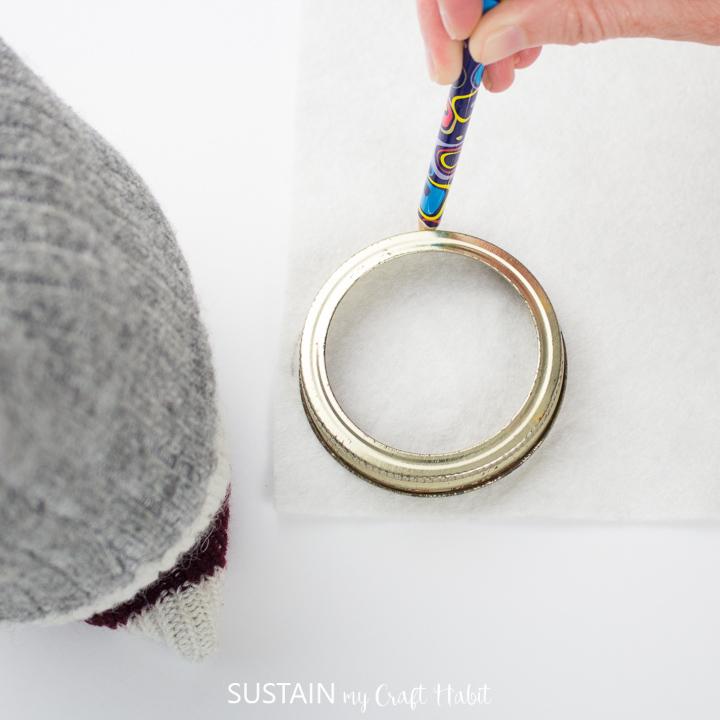 Tracing circles onto a felt sheet using a mason jar lid and pencil.