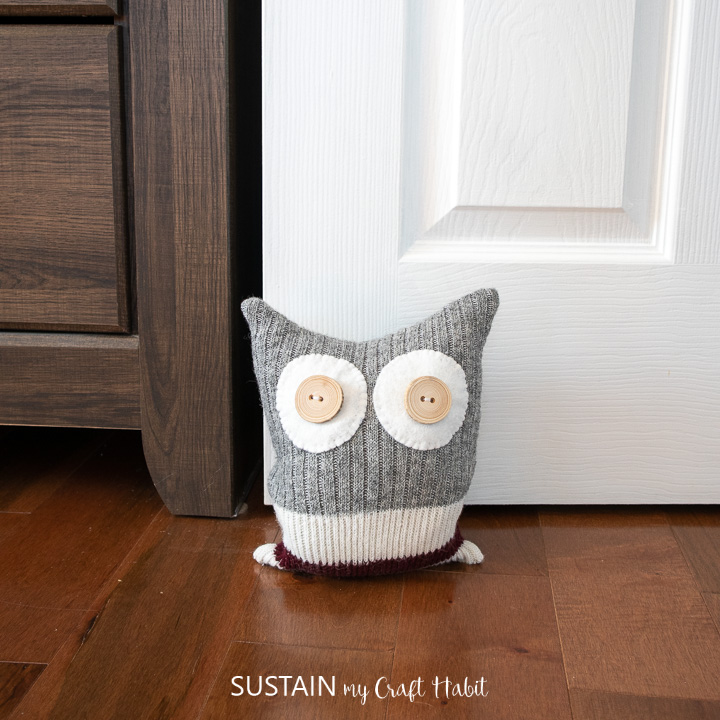 an upcycled owl doort stop holding open a bedroom door