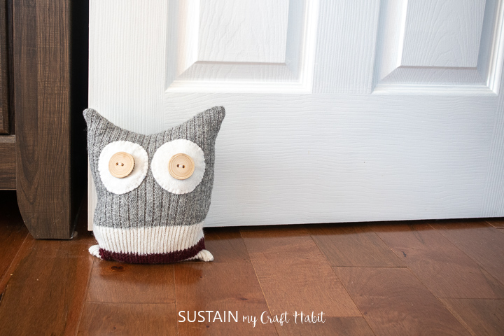 Upcycled sock owl door stop placed in front of a door to hold it open.