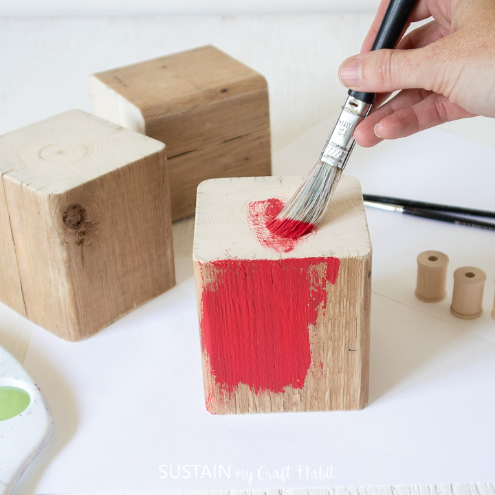 Painting a wood block red.