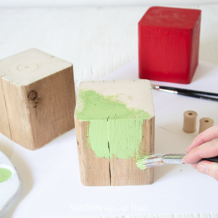 Painting a wood block green.