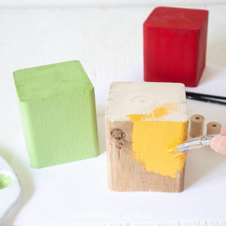 Painting a wood block yellow.