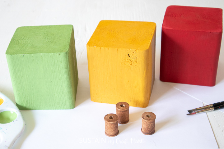 Painted wood blocks and wooden spools.