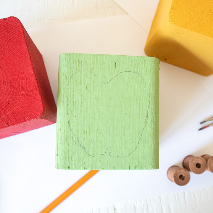 Drawing the outline of an apple on the green painted wood block.