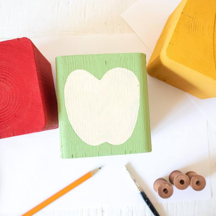Painting a  half apple on a green wooden block.
