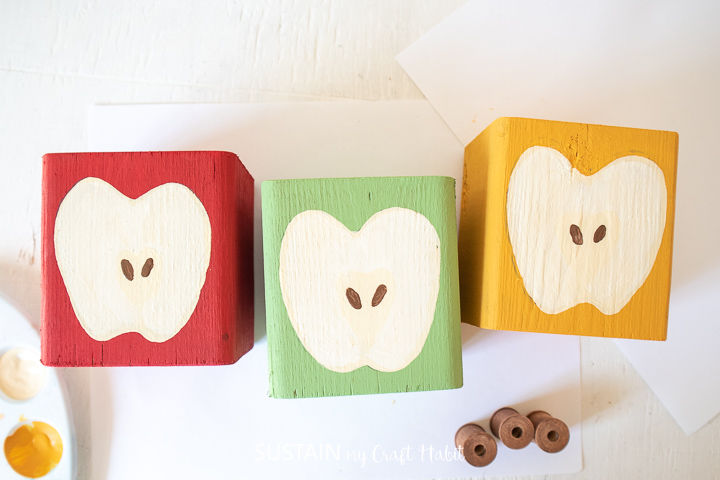 Painting two apple seeds in the center of each wood block apple.