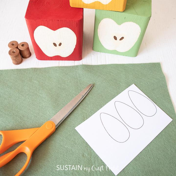 Felt fabric, scissors and a leaf stencil.