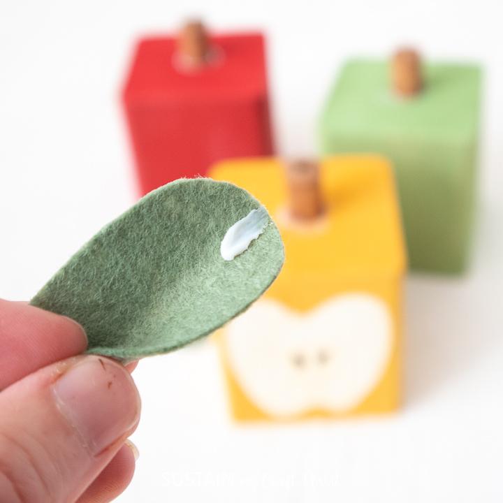 Adding glue to the felt leaf shape.