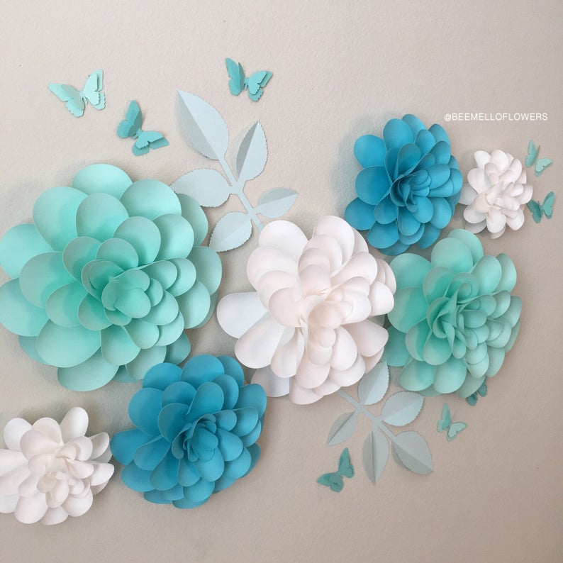 An arrangement of blue, white adn teal large paper flowers on a beige wall.