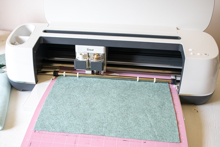 Cricut machine being loaded with felt fabric.