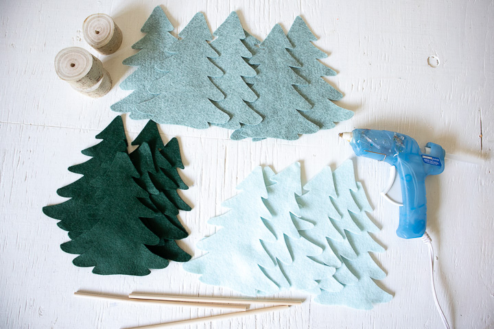 Cut out felt Christmas trees next to wooden dowels, small tree stump and hot glue gun.