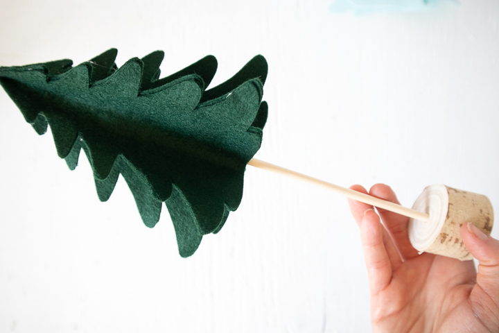 Inserting the wooden dowel into the 3D felt Christmas tree.