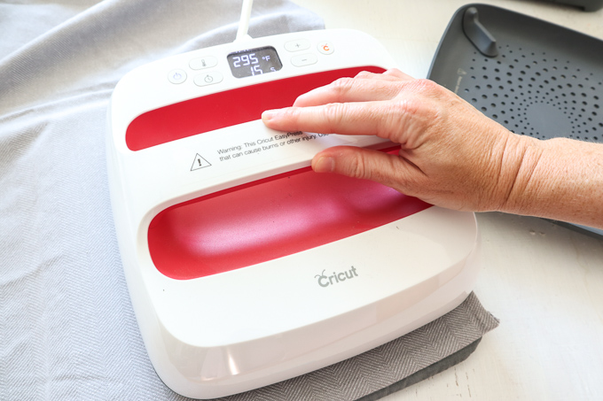 Pressing the EasyPress 2 machine over the lettering and tea towel.