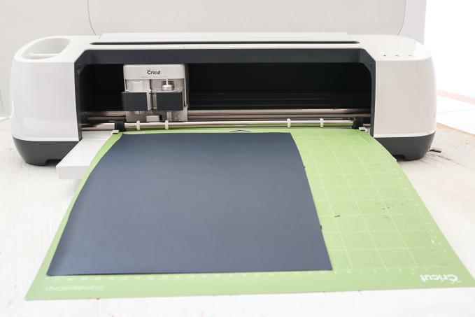 Placing black vinyl onto the standard grip map for Cricut.