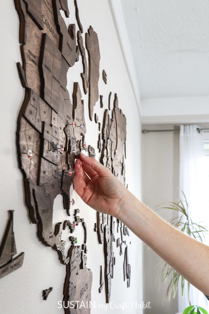 Using the country push pins to mark your travels on Enjoy the Wood's 3D world map wood wall art