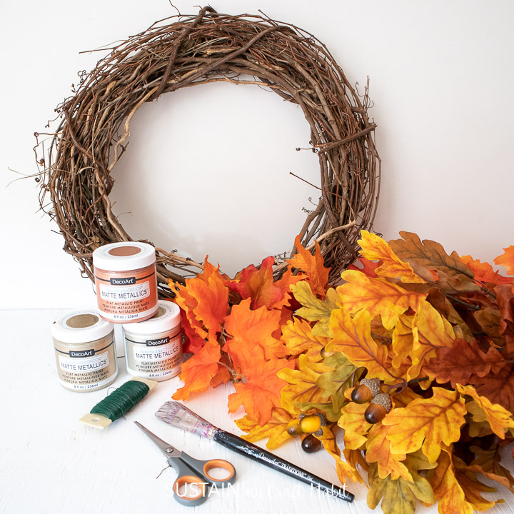 Gathering the supplies needed to make a DIY metallic fall leaf wreath.