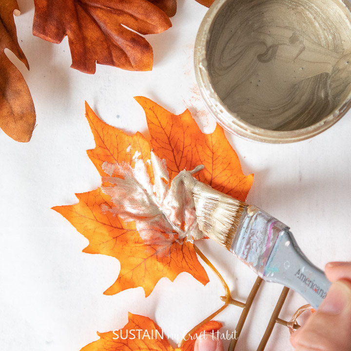 Painting a faux maple leaf with Champagne Metallic paint.