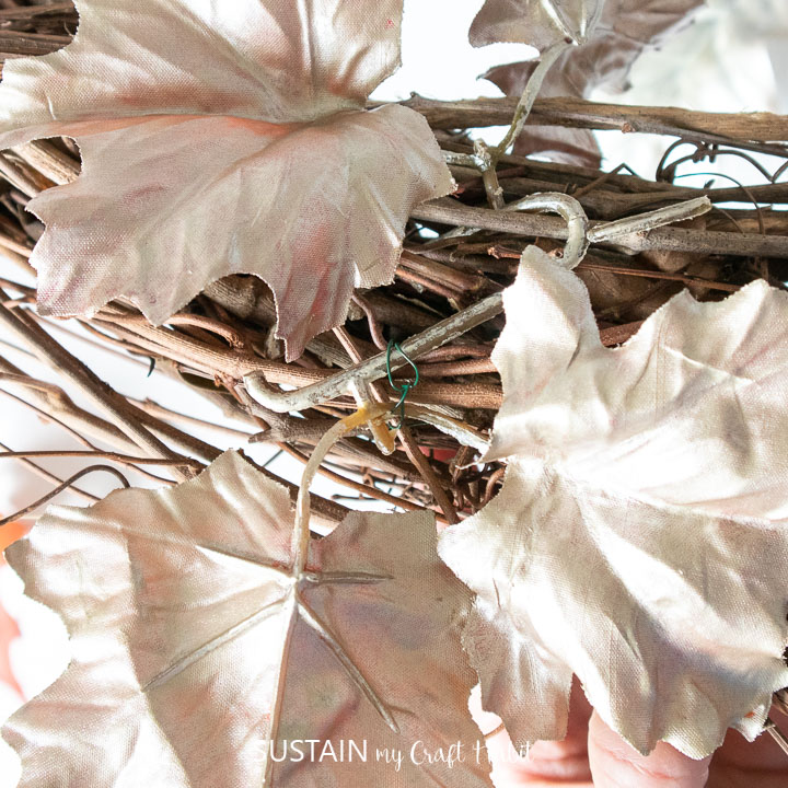 Using floral wire to secure painted faux leaves onto a grapevine wreath.