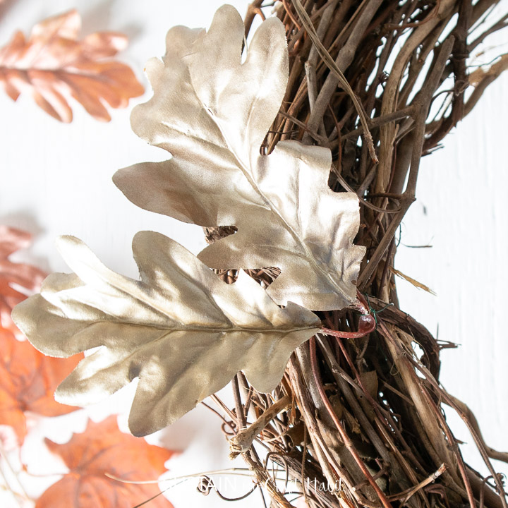 Securing painted faux oak leaves onto a grapevine wreath.