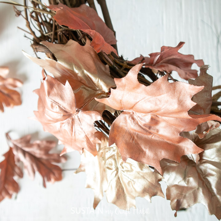 Adding painted faux maple leaves to the grapevine wreath.