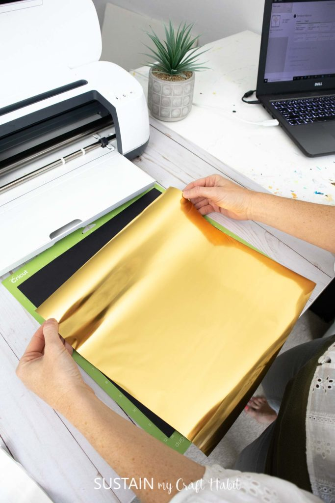 placing a sheet of gold foil on to a piece of cardstock to test the Cricut foil transfer system
