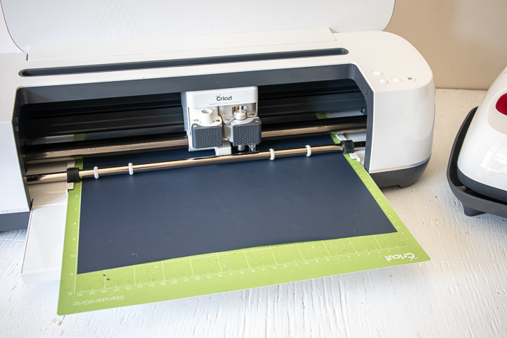 Cricut machine cutting the black vinyl.