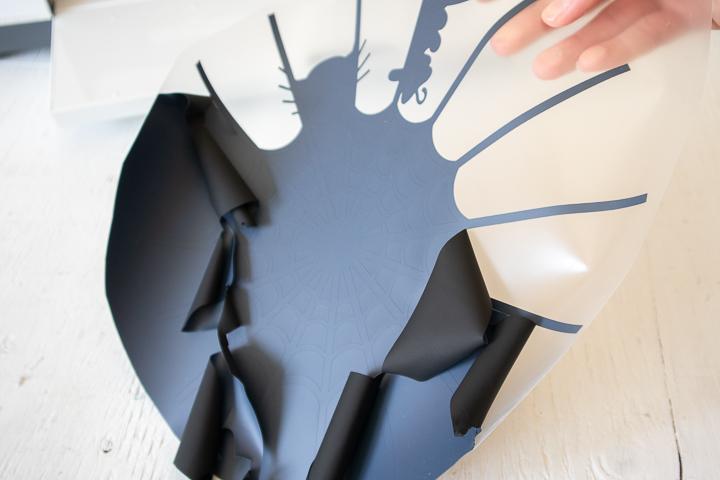 Peeling away excess black vinyl from the cut image.