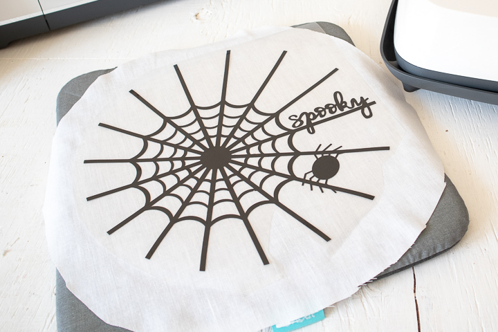 Placing the spider web cut image onto the fabric.