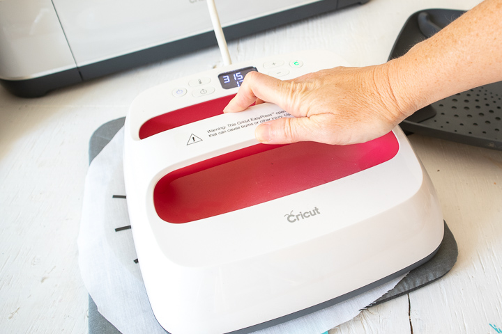 Pressing the EasyPress 2 machine onto the spider web cut image and fabric.