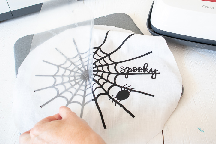 Peeling away plastic layer of vinyl on top of the cut spider web image.