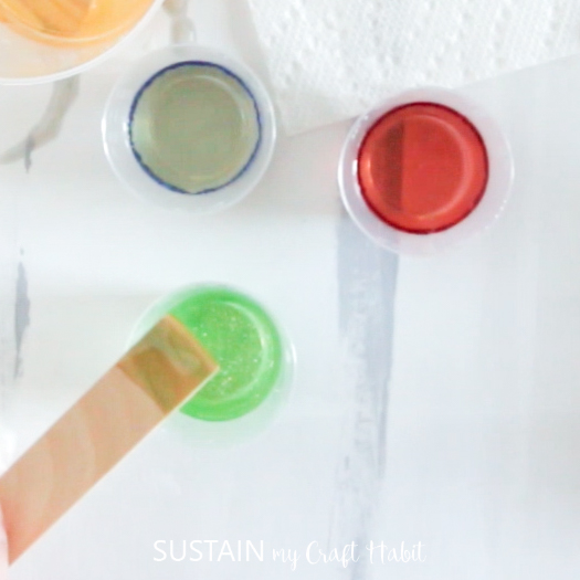 Adding glitter to the resin mixture with a wooden craft stick.