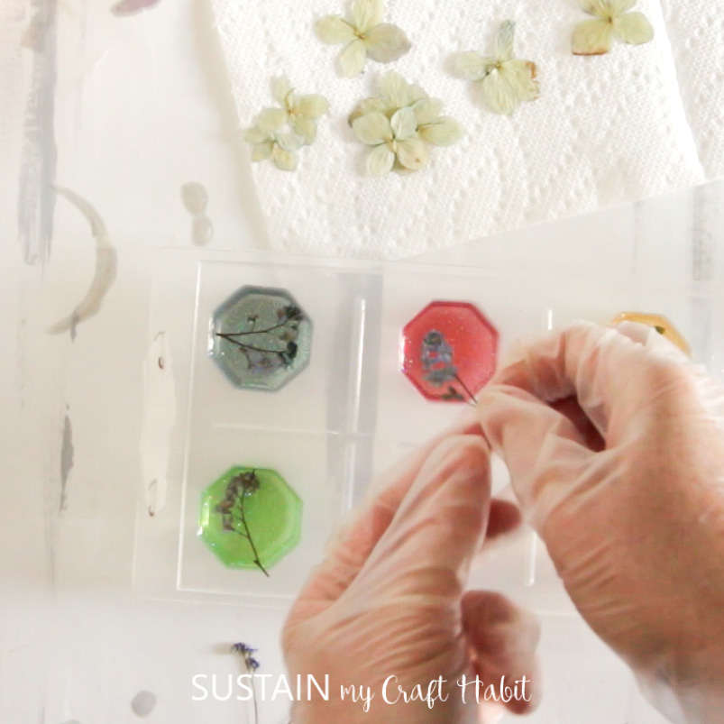 Adding more resin to cover the dried flower in the resin mold.