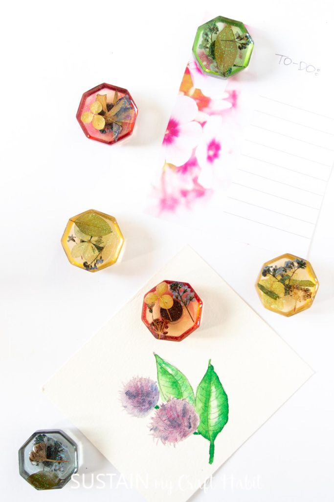 Resin fridge magnets holding up note cards.