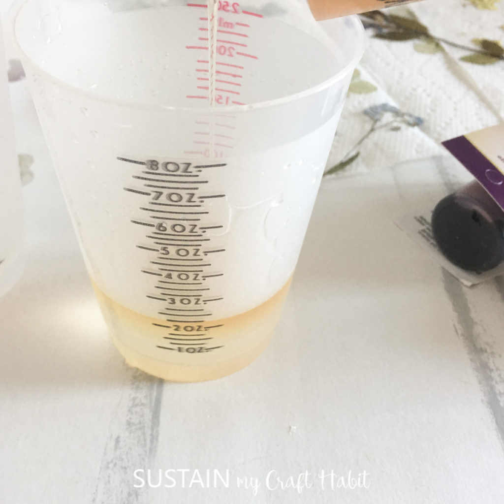 Pouring epoxy and hardener into a small measuring cup.