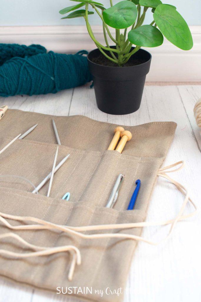 knitting neelde organizer holding various sized needles and crochet hooks