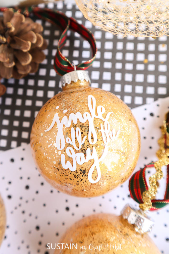 """Close up of the vinyl words """"jingle all the way"""" on the glittering gold painted glass ornament."""