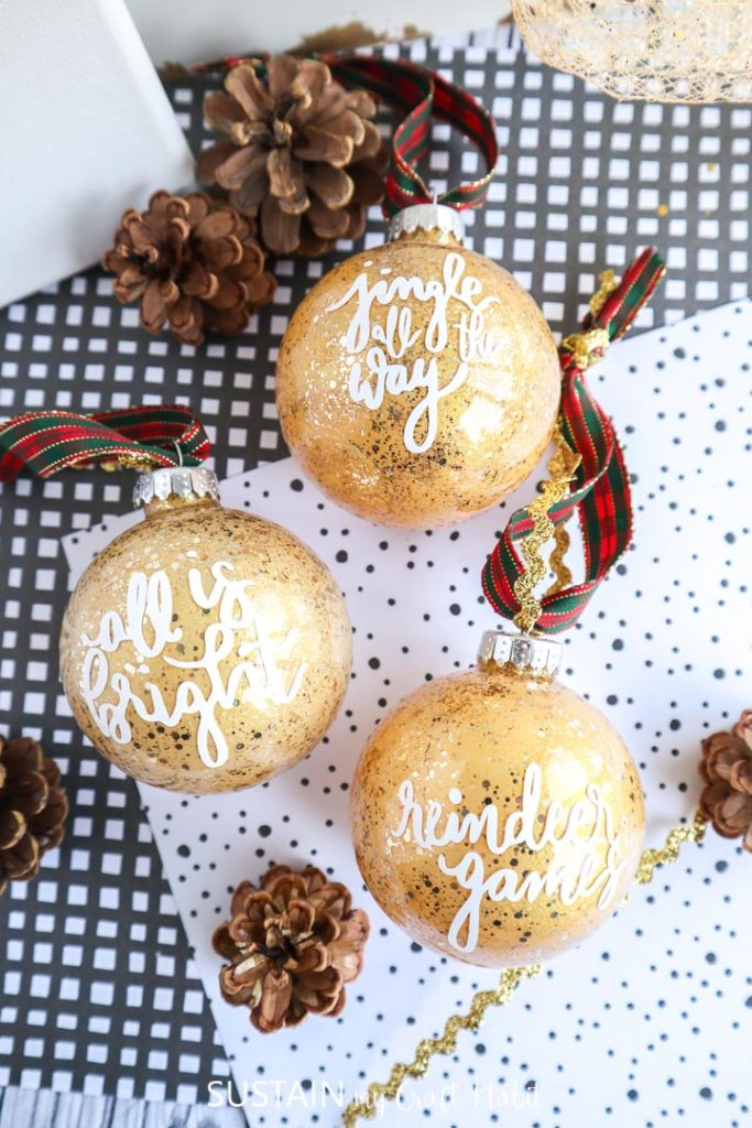 Glittering gold painted glass ornaments. with vinyl sayings on the front.