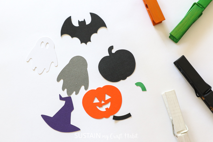 Laying the cut Halloween images down next to the painted clothespins.