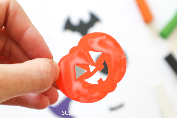 Cut jack-o-lantern pumpkin card stock.