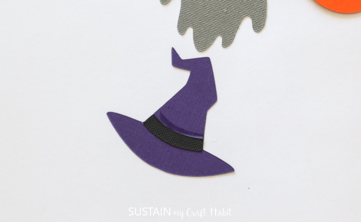 Gluing a black band on the purple witch catch.
