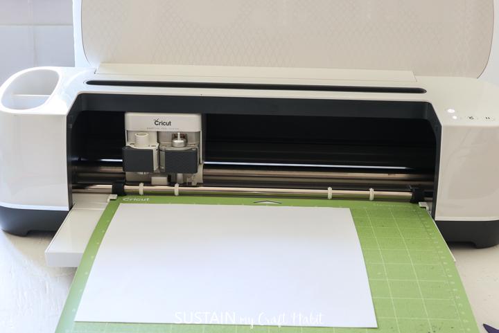 Loading white card stock into the Cricut machine.