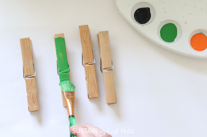 Painting one of the four clothespins green.