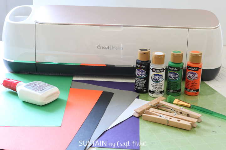 Materials needed for clothespin crafts for Halloween including card stock, Cricut machine, paint, glue and clothespins.