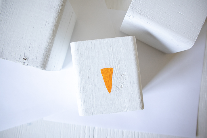 Painting an orange triangle on the wood block.