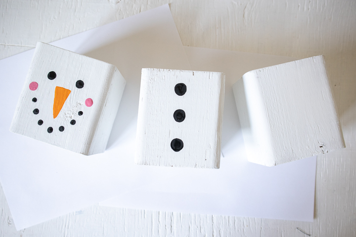 Painting black circles on another wood block to resemble snowman buttons.
